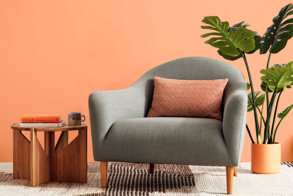 Light blue chair with orange background and minimalist decor surrounding it
