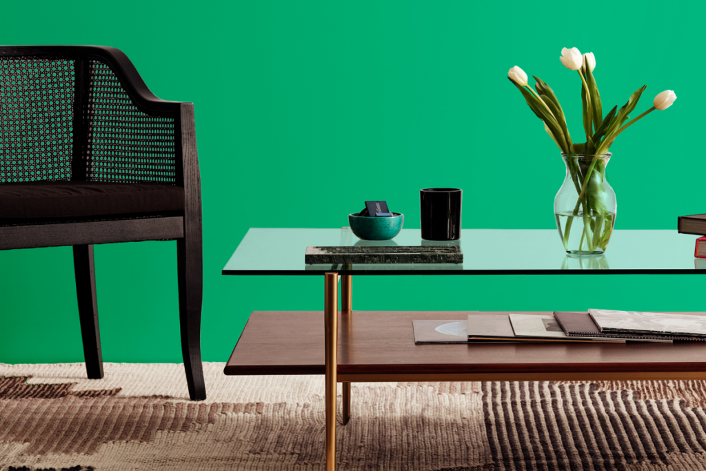 Living room with glass and wood coffee table, black accent chair, and various small decor, kelly green backdrop and wool rug