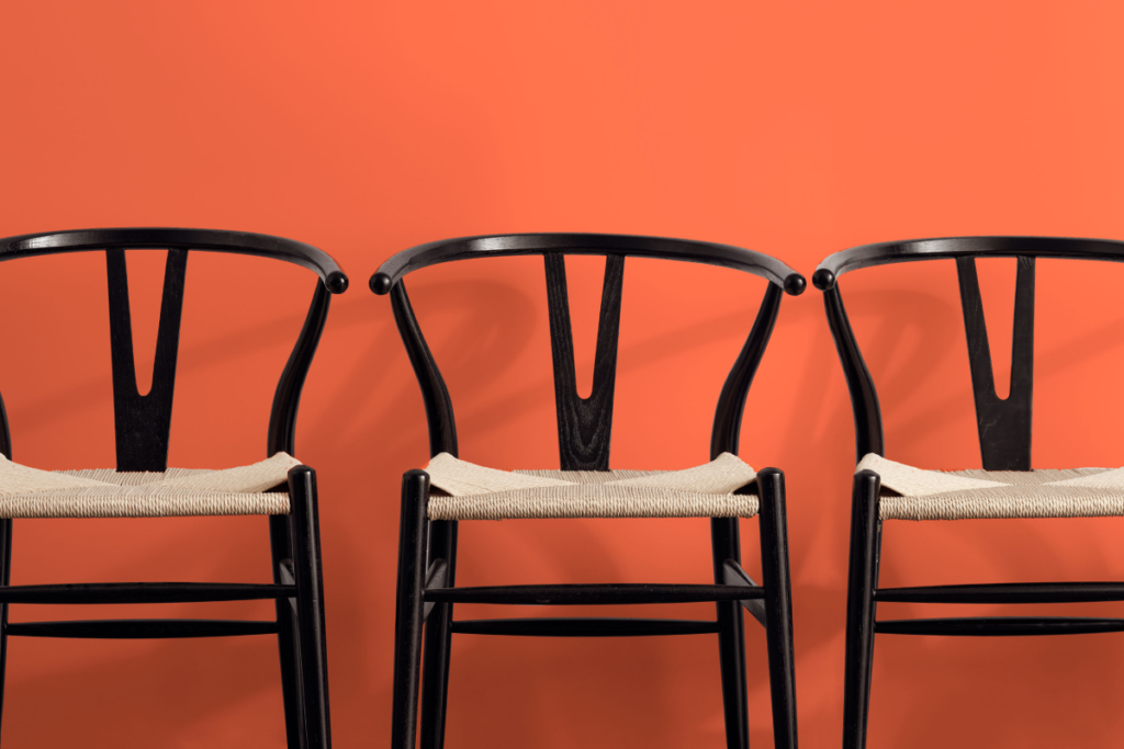 3 black wishbone chairs side-by-side with an orange backdrop