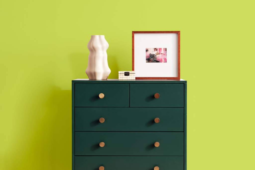Forest green dresser with gold knobs and light decor on top, lime green backdrop